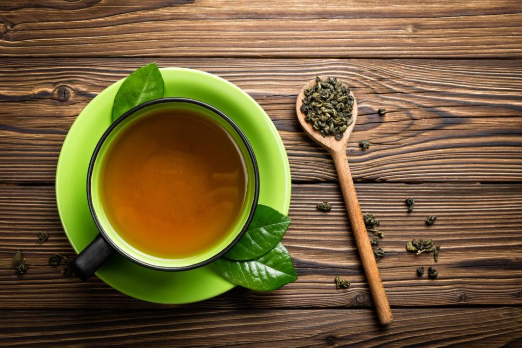 Green Tea In Cup With Tea Leaves On Wooden Spoon 1024x683